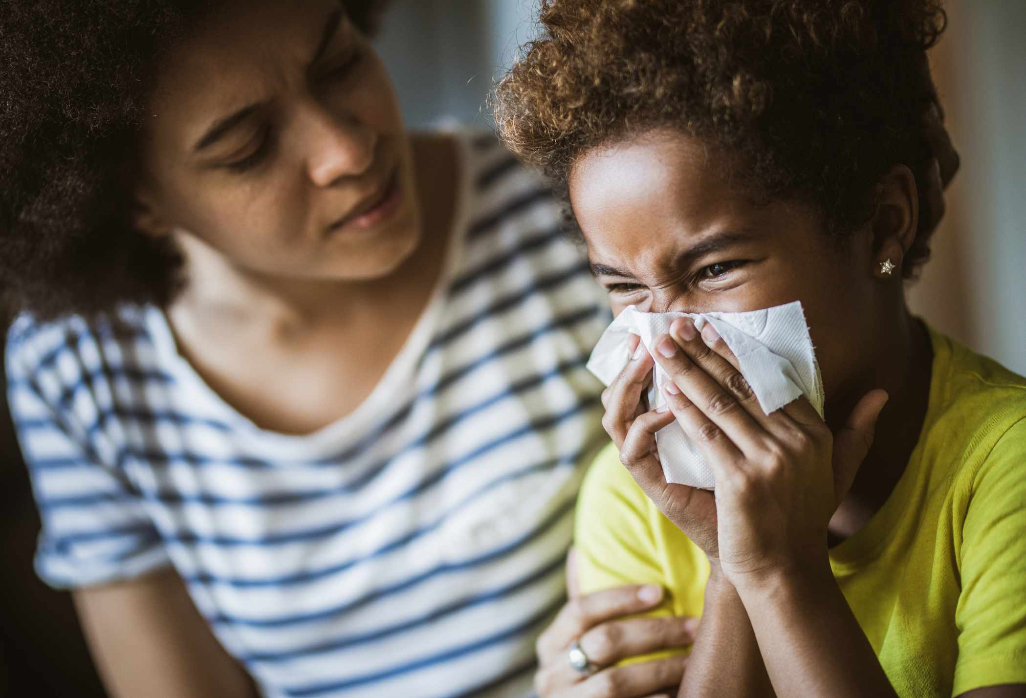 Woman of color looking concerned at child of color blowing nose