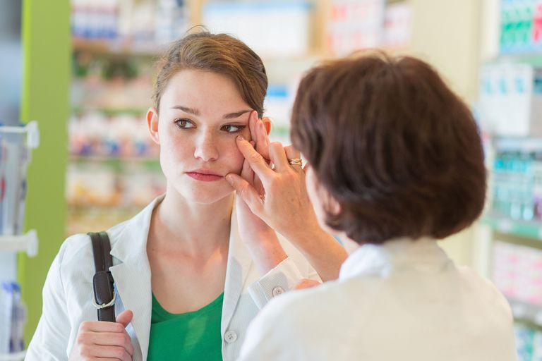 Pharmacist examining womans eye.
