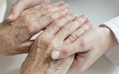 Female doctor examining senior patients hands