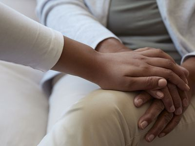 Unrecognisable young woman holding hands of another woman.