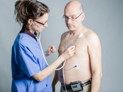 Nurse listening man's heart while wearing holter monitor