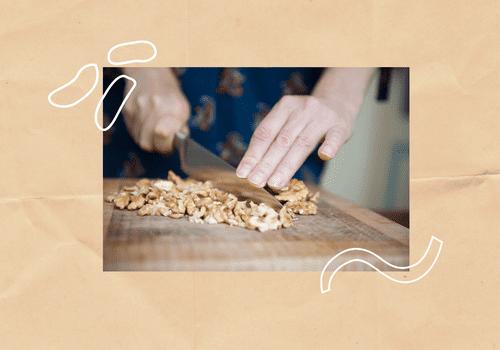 Woman cutting walnuts on a cutting board.