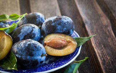 Fresh ripe blue plums on plate