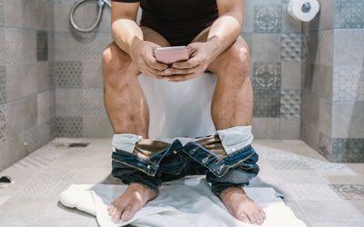 Man sitting on a toilet bowl