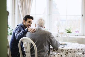 Happy caretaker communicating to senior man in nursing home