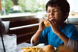 Boy eating cheeseburger