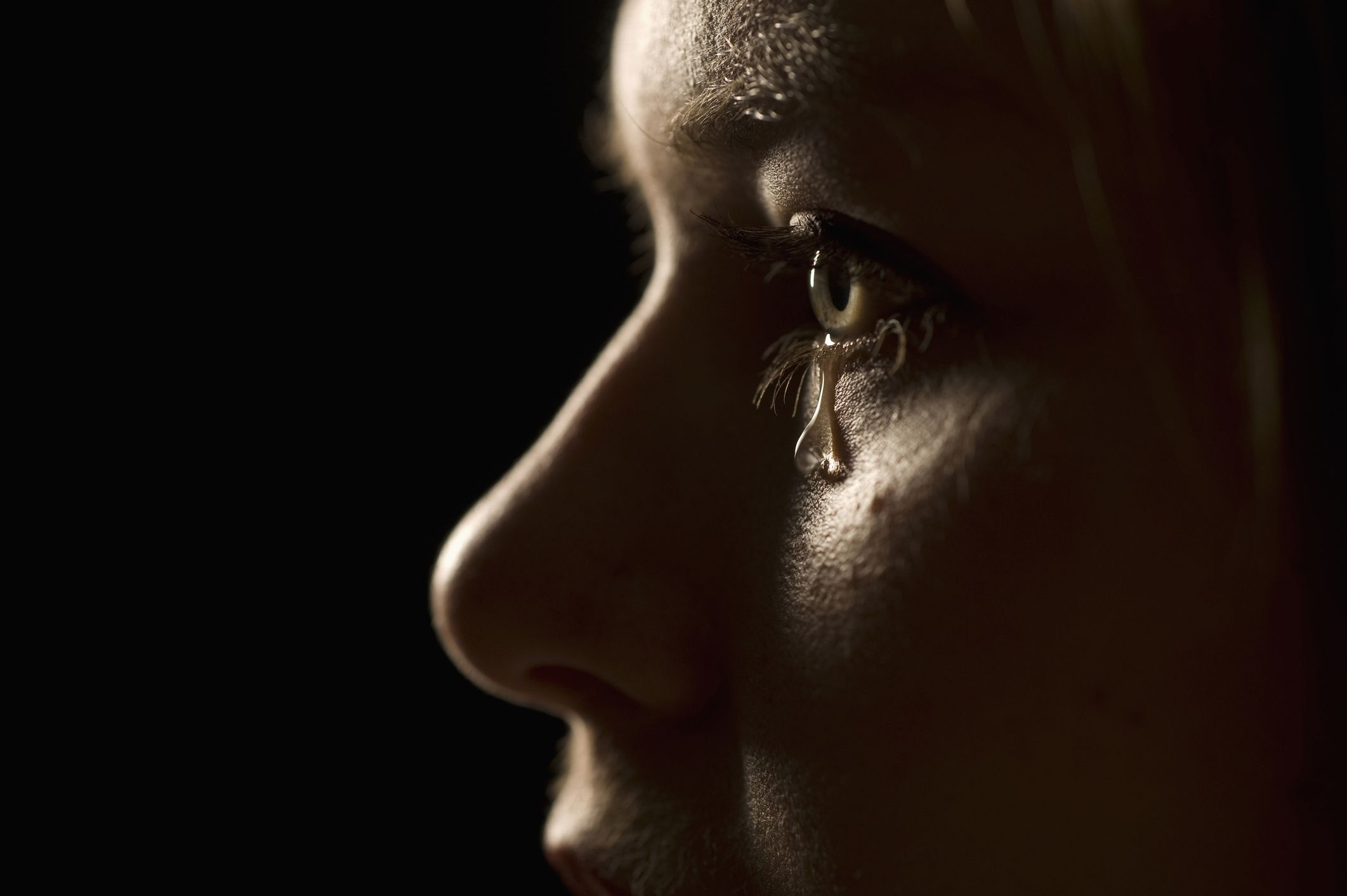 Young woman in profile crying close up