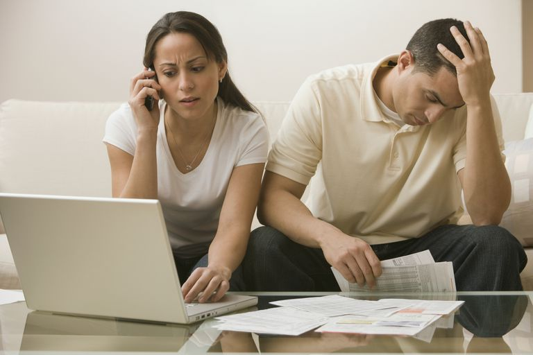 woman on phone while a man looks stressed holding bills