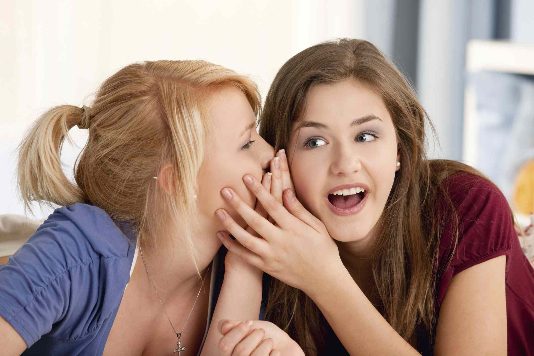 Two teenage girls whispering in their room
