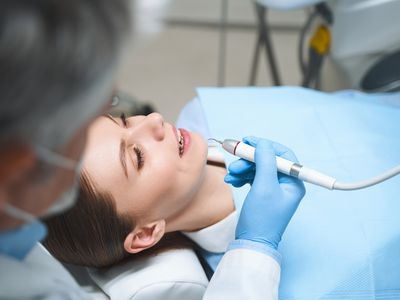 Dentist is treating young woman stock photo