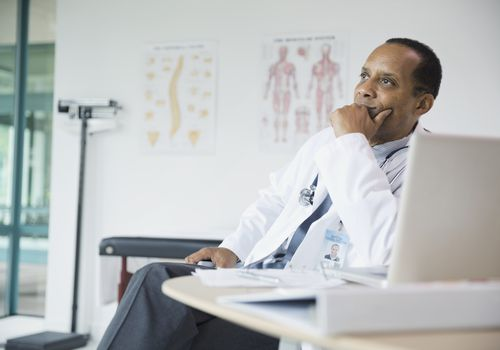Thoughtful male doctor sitting at desk in hospital