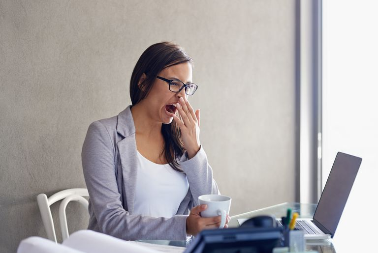 Woman yawning at work.