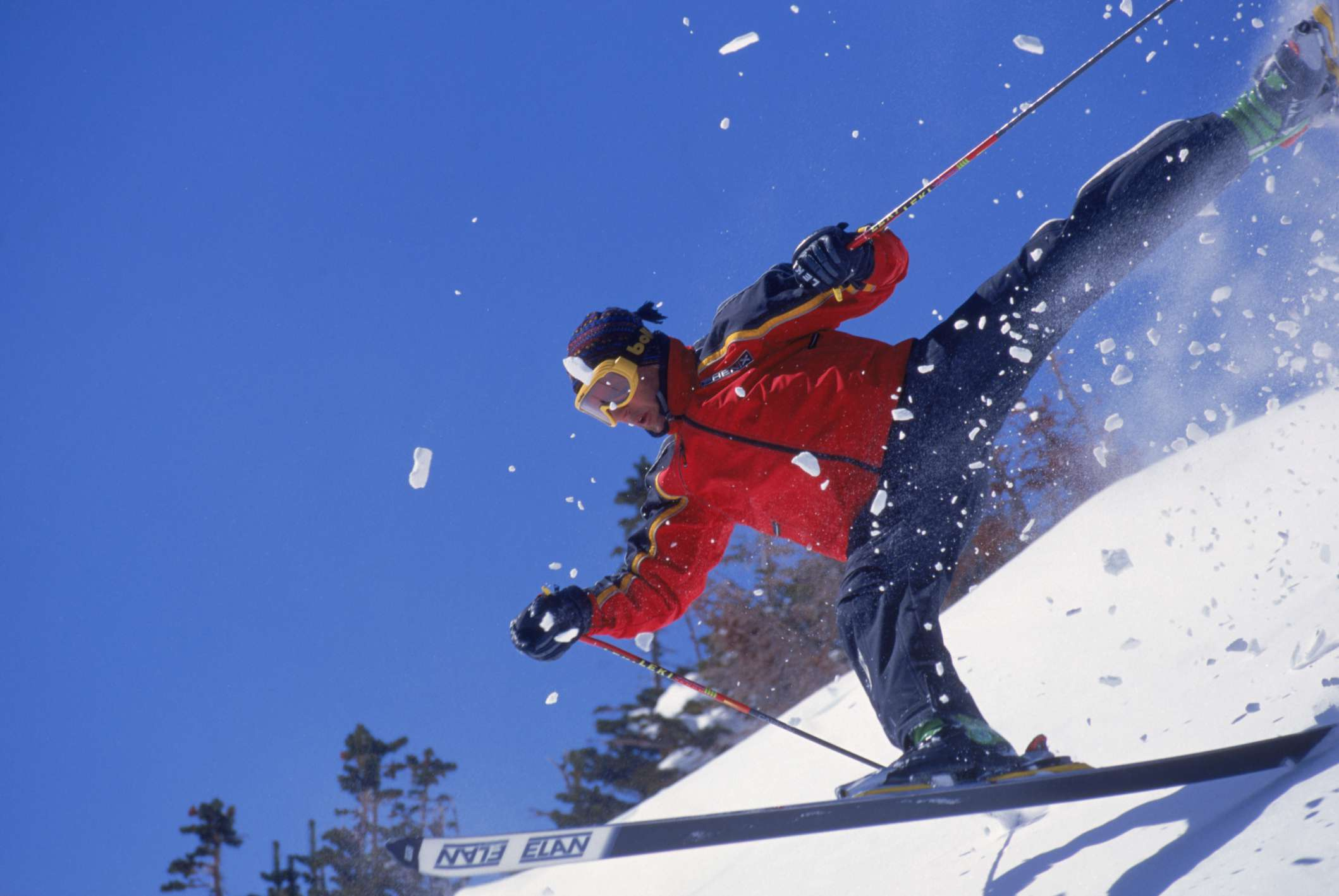 A skier falling on the side of a mountain