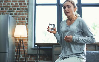 A woman in her living room sweating and holding a glass of water