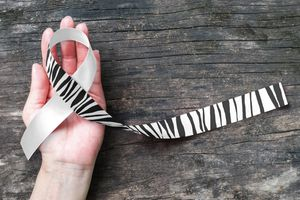Carcinoid Cancer Awareness ribbon zebra stripe pattern on helping hand support and old aged wood