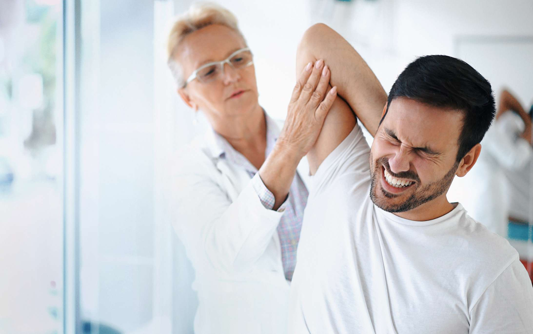 Woman examining a man's shoulder as he grimaces in pain