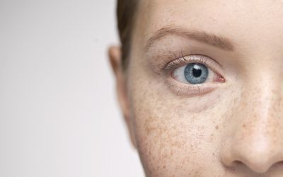 Close up of young woman's blue eyes, freckles