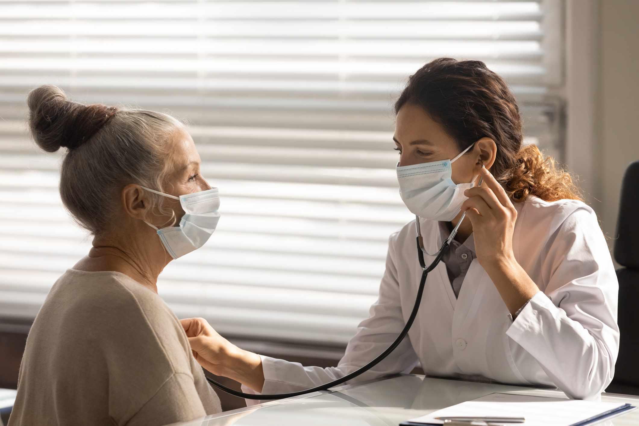 Female doctor listen to senior patient heart