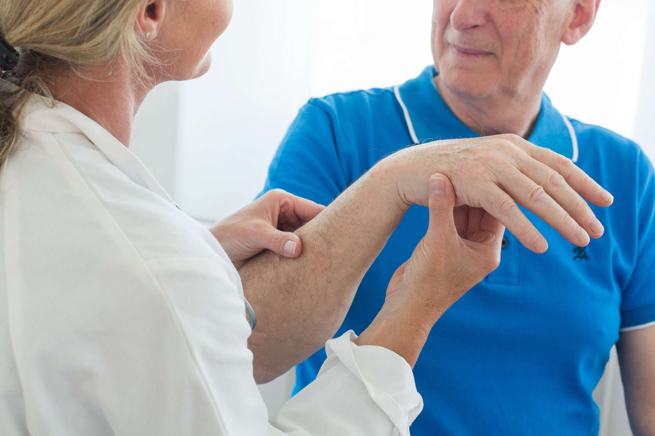older man with wrist pain talking to doctor