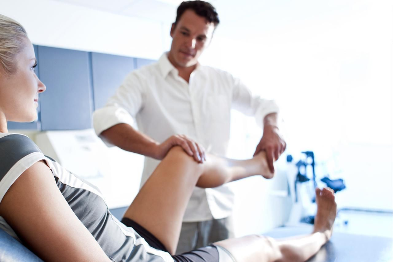 physical therapist working on patient's knee