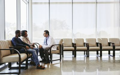 Doctor sitting down and speaking with couple
