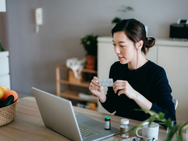 Young Asian woman video conferencing with laptop to connect with her family doctor, consulting about medicine during self isolation at home in Covid-19 health crisis