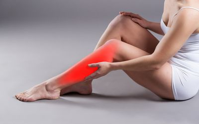 A woman's calf is colored red along the outside, where the superficial peroneal nerve runs.