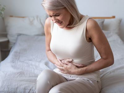 Unhealthy mature woman holding belly, suffering from pain