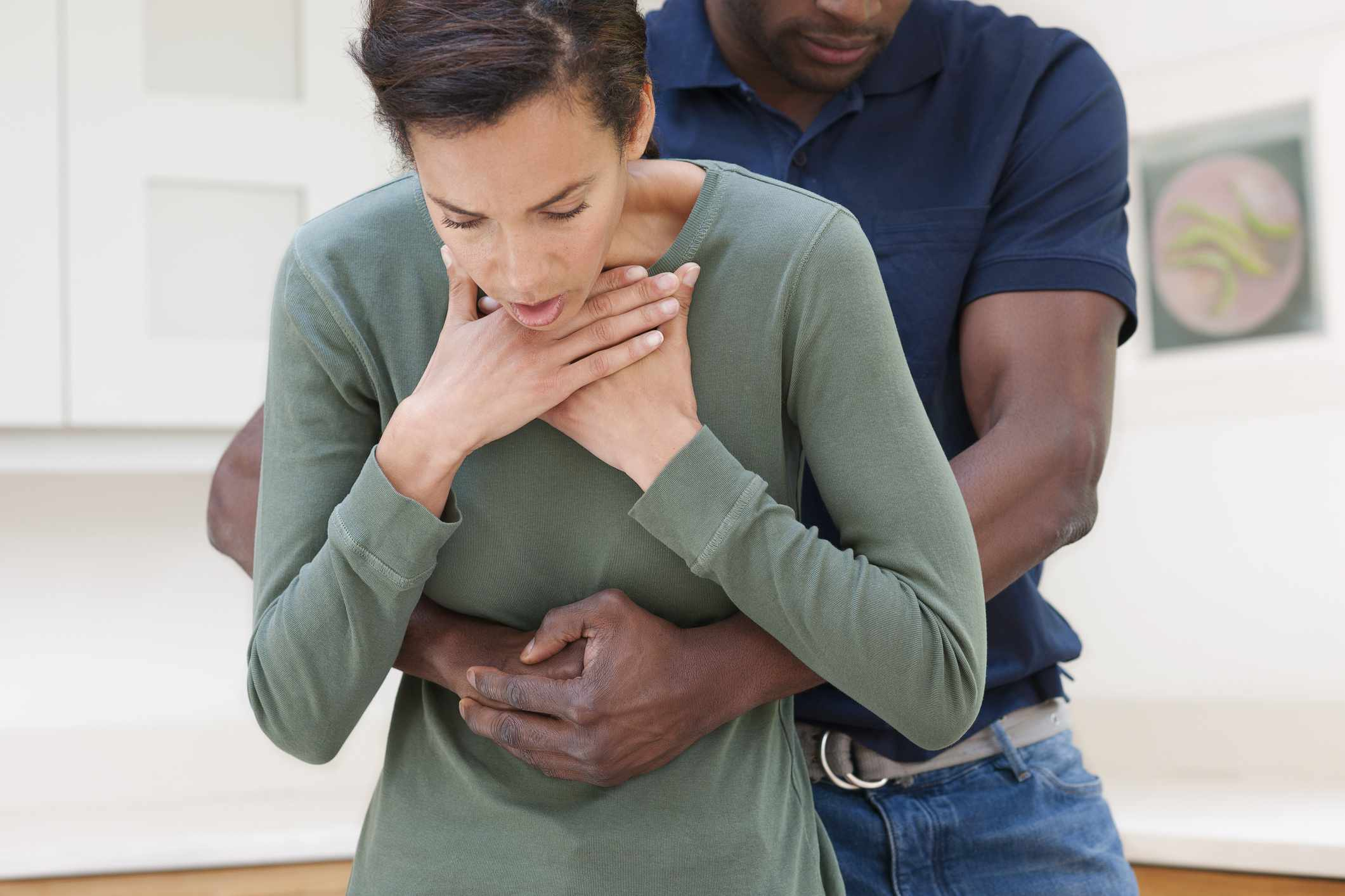 Man performing the Heimlich manoeuvre on a choking woman