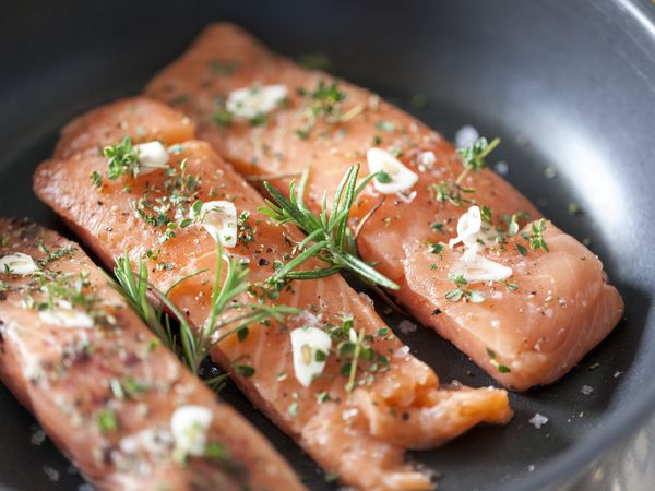 Delicious salmon fillet in a pan with garlic and herbs