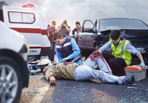 Man on the ground bleeding with paramedics