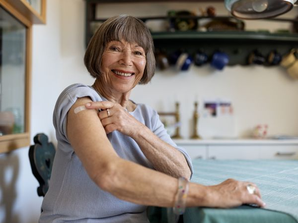 Senior woman looking at camera pointing at her arm with a bandage after getting vaccine