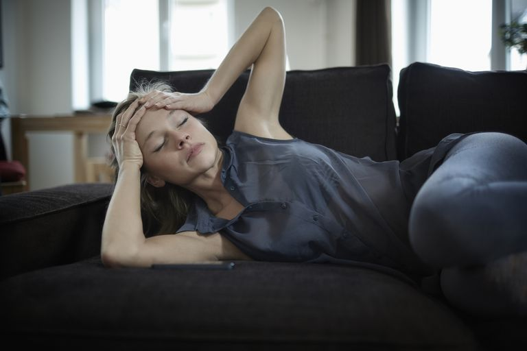 Young woman lying on couch with head in hands