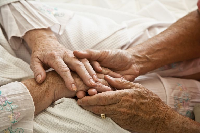 close up of old people's hands holding