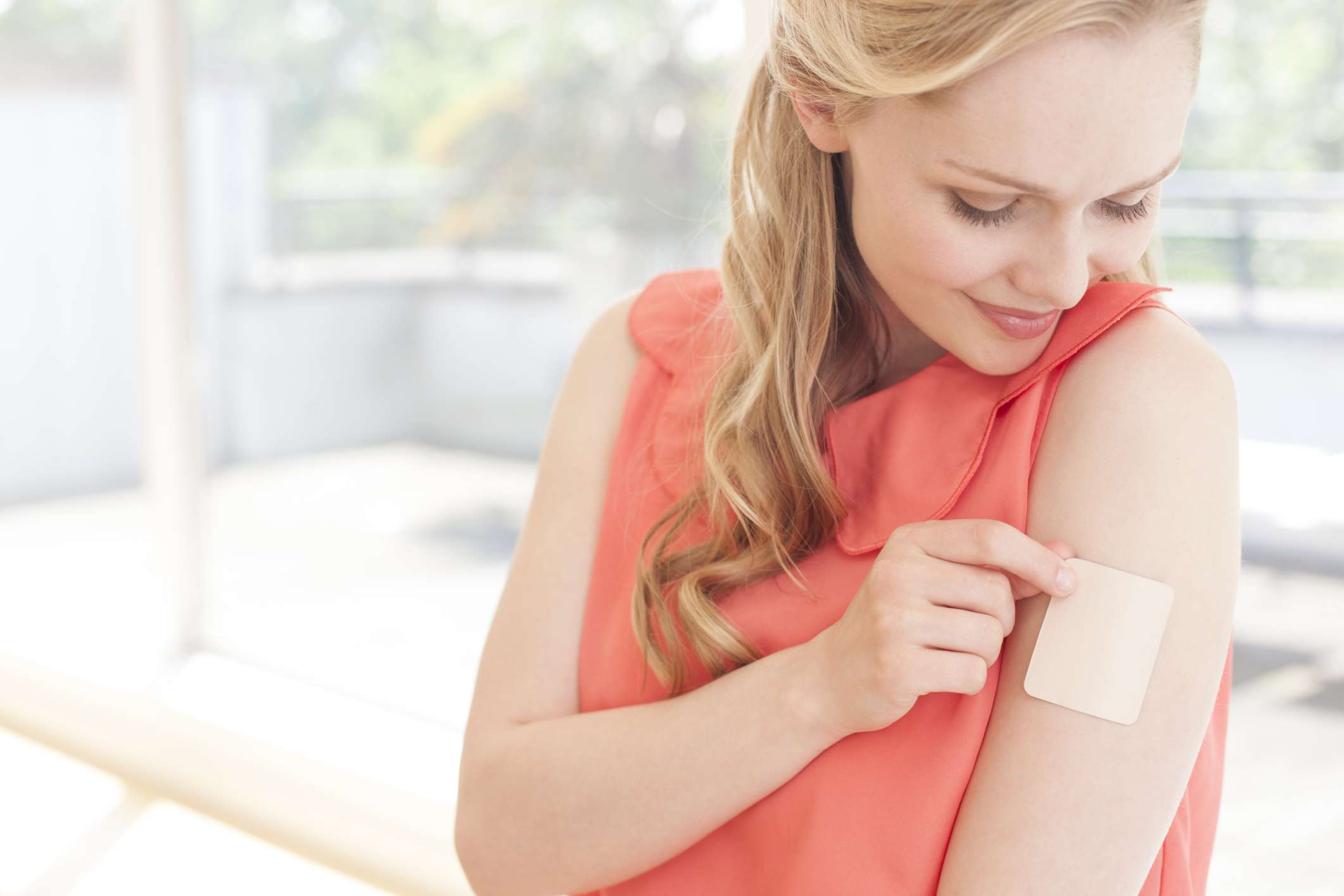 Woman putting contraception patch on arm