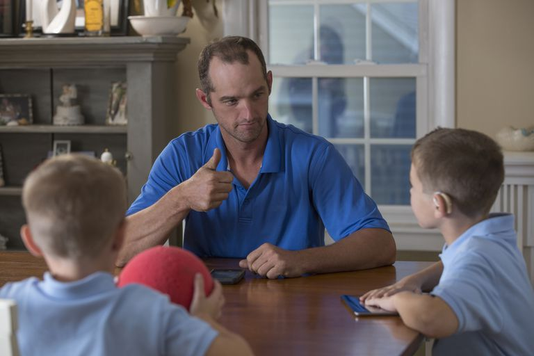 Caucasian father and sons signing at dinner table