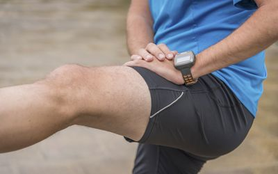 Male runner stretching his thigh muscle
