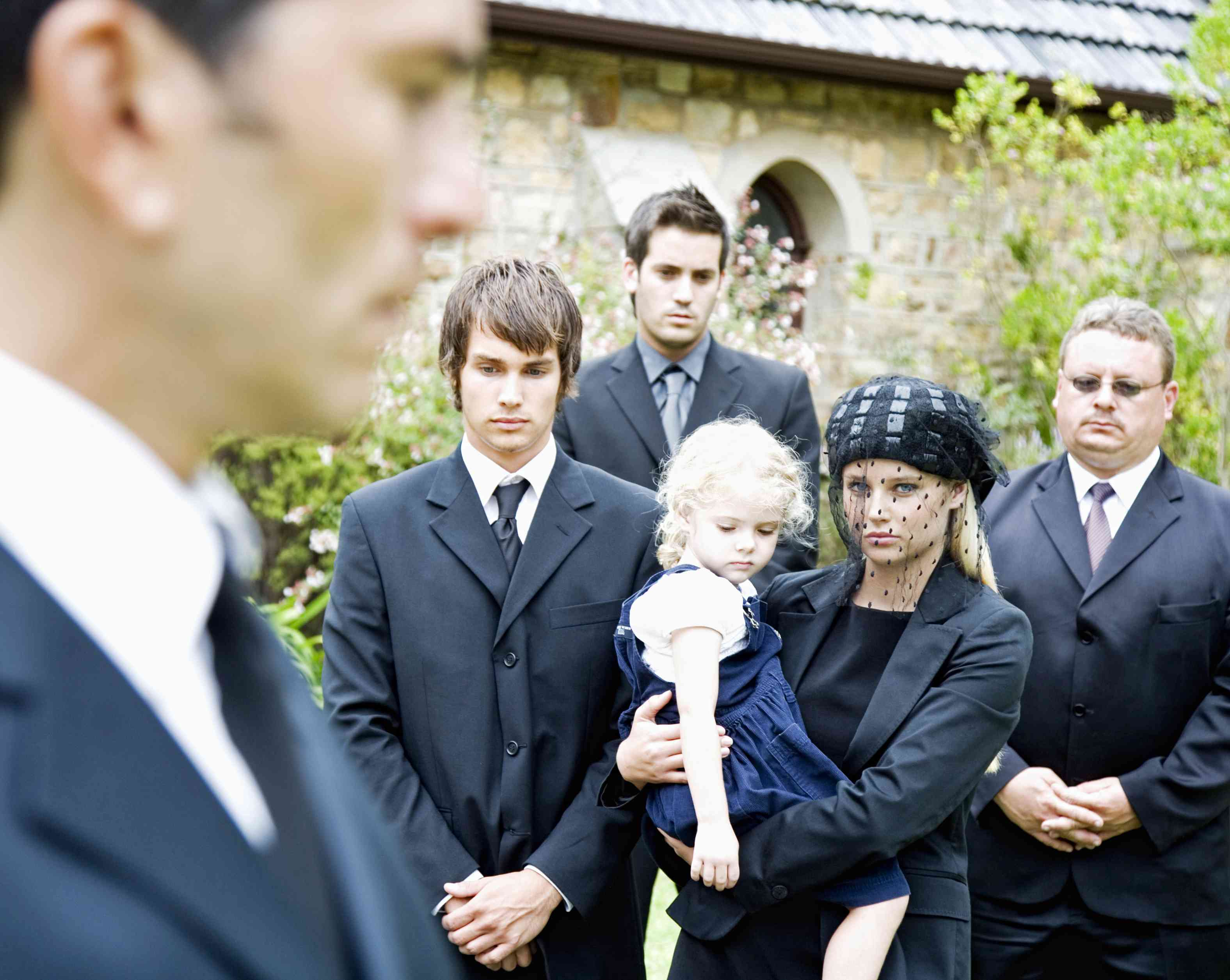 Adults and young child at a funeral service outside