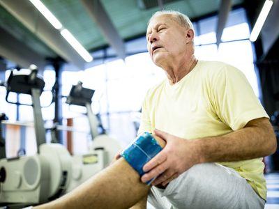 Senior man holding ice pack on knee