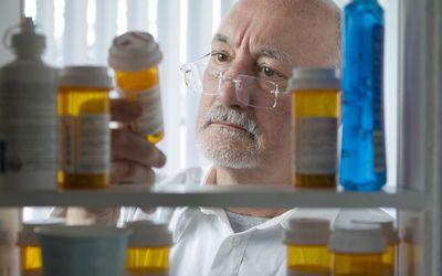 Man looking at prescriptions in medicine cabinet