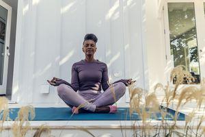 Mature woman meditating in backyard