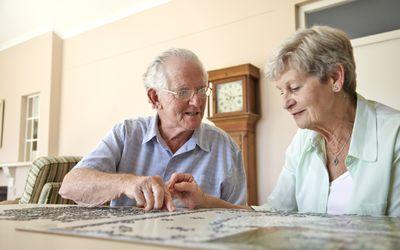 Elderly couple doing jigsaw puzzle
