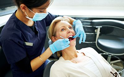 A woman having her teeth checked by the dentist