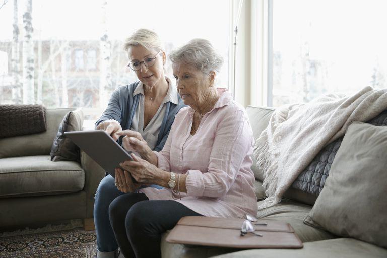 Daughter helping senior mother using digital tablet - stock photo