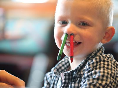 Kid with crayons stuck up his nose.