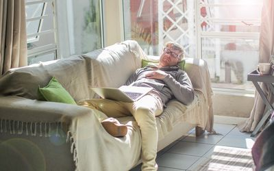 A picture of a man asleep on the couch with a computer on his lap.