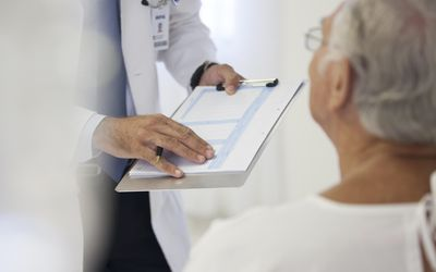 Doctor showing medical chart to patient in hospital room