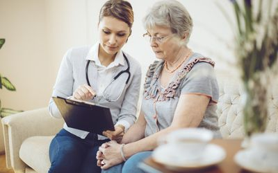 Doctor showing older woman results on ipad