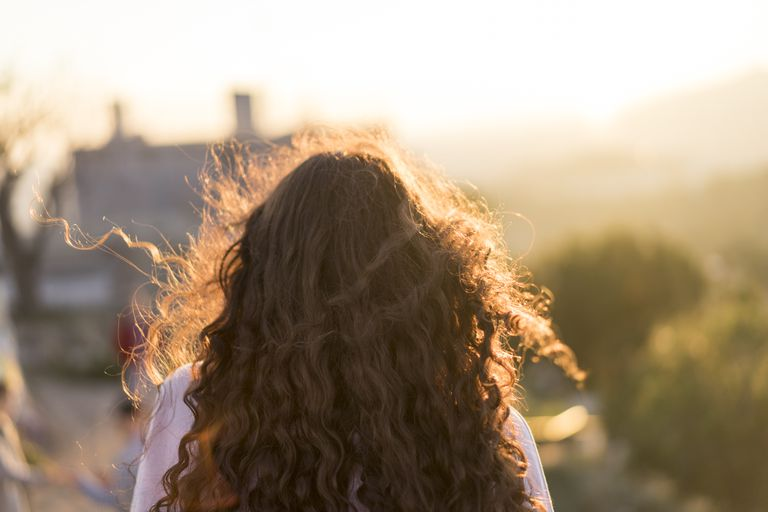 Back view of young woman with long curly hair at sunset