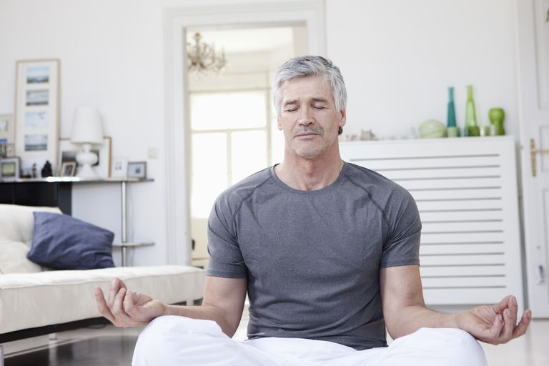 Mature man meditating in his living room